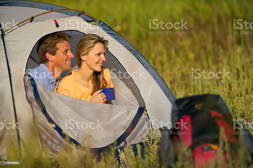 Couple Peering from Camping Tent royalty-free stock photo