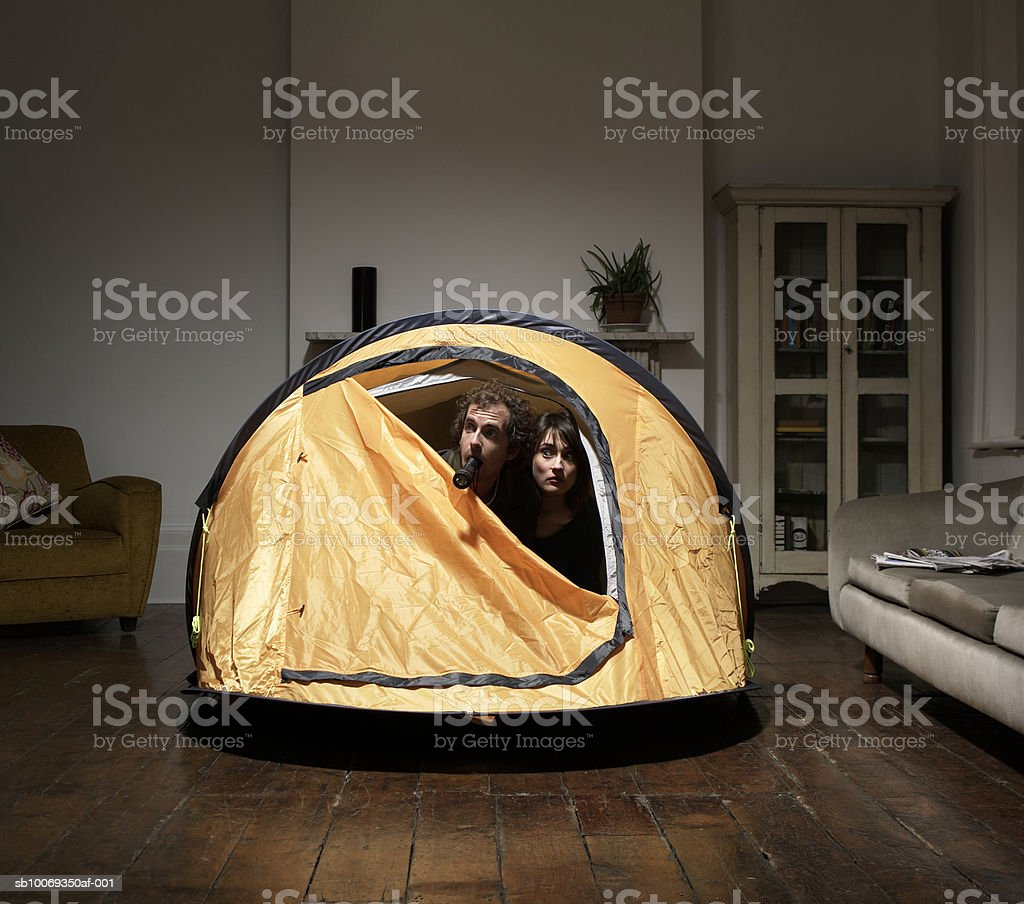 Couple peering from tent in living room royalty-free stock photo