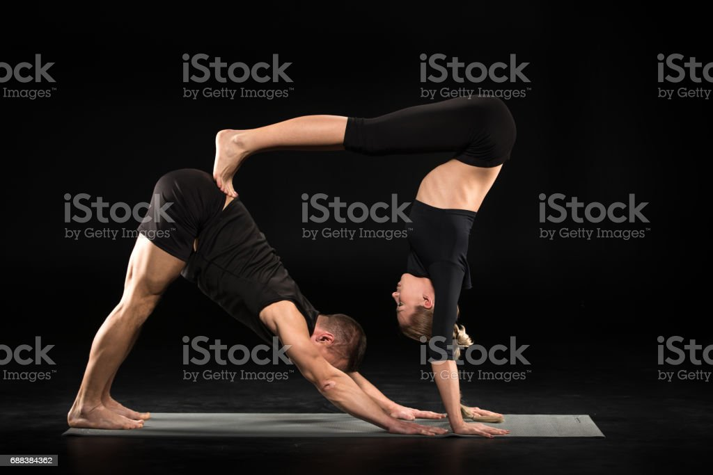 Couple performing acroyoga stock photo