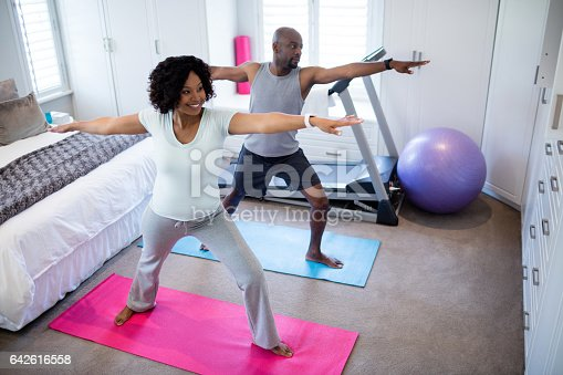 istock Couple performing exercise in bedroom 642616558