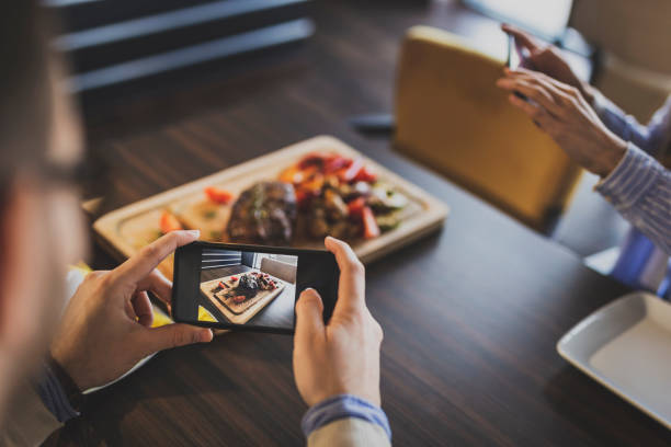 couple photographing food in a restaurant - foodie stock photos and pictures