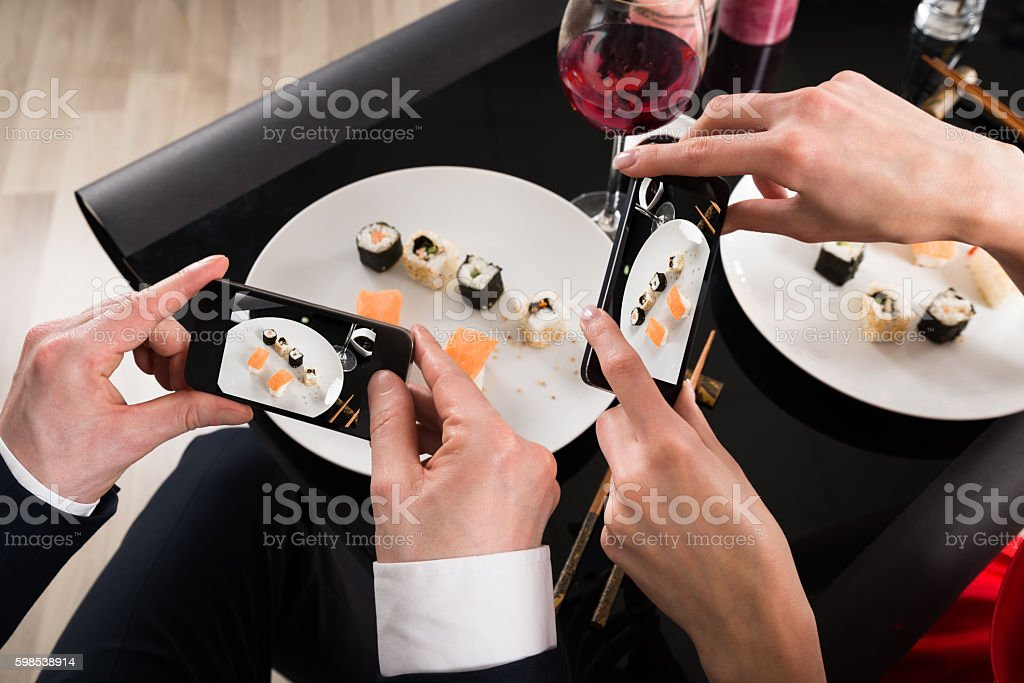 Couple Photographing Food With Smartphones photo libre de droits