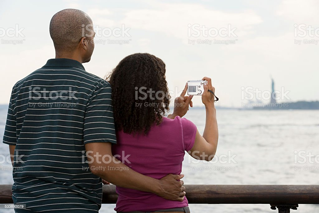 Couple photographing statue of liberty stock photo