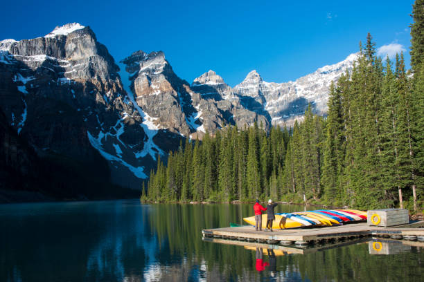A couple photographing Ten Peaks in the morning at Moraine Lake in Banff National Park Lake Louise, Canada - June 22, 2015. A couple photographing Ten Peaks in the morning at Moraine Lake in Banff National Park, Alberta, Canada. valley of the ten peaks stock pictures, royalty-free photos & images