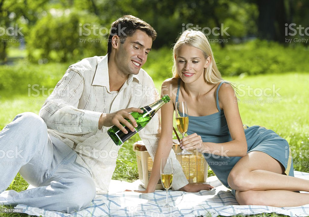 A couple picnicking outdoor holding a bottle of champagne royalty-free stock photo