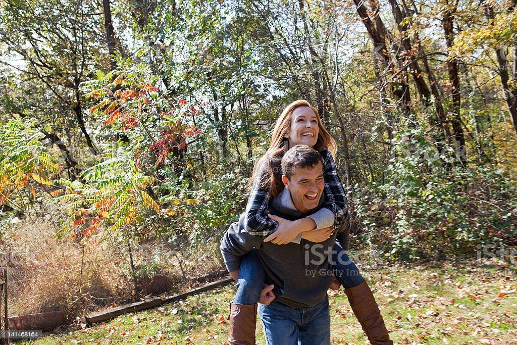Couple piggybacking outdoors stock photo
