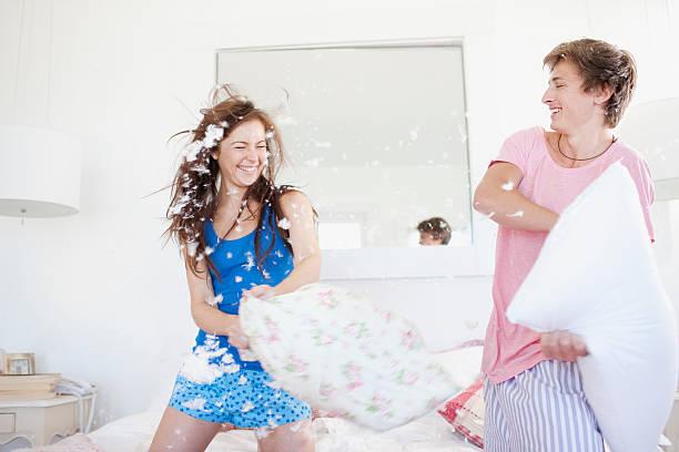paar kissen kämpfe im schlafzimmer - kissenschlacht paar stock-fotos und bilder