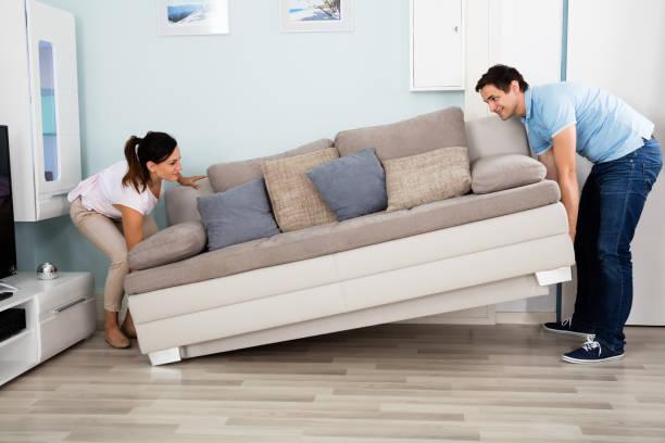 Couple, plaçant le canapé dans le salon - Photo