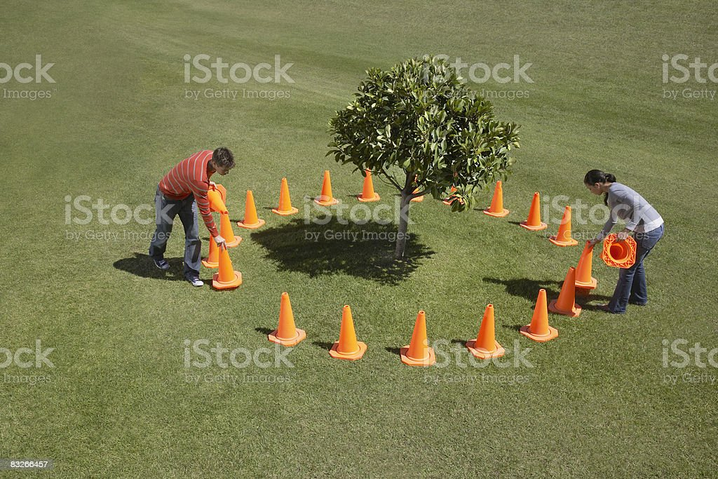 Couple placing traffic cones around tree royalty-free stock photo