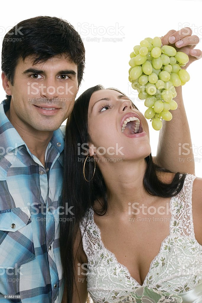 Couple playfully eating grapes royalty-free stock photo