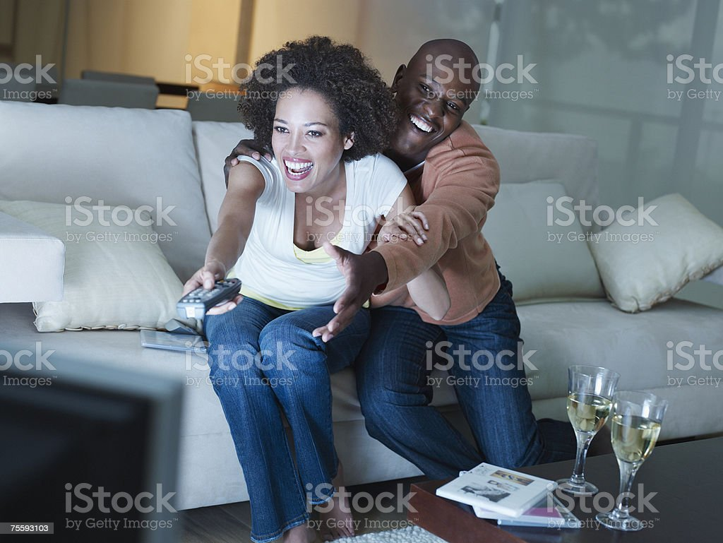 A couple playfully fighting over the television remote stock photo