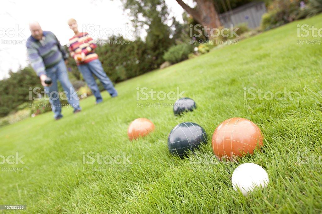 Couple playing bocce ball - horizontal stock photo