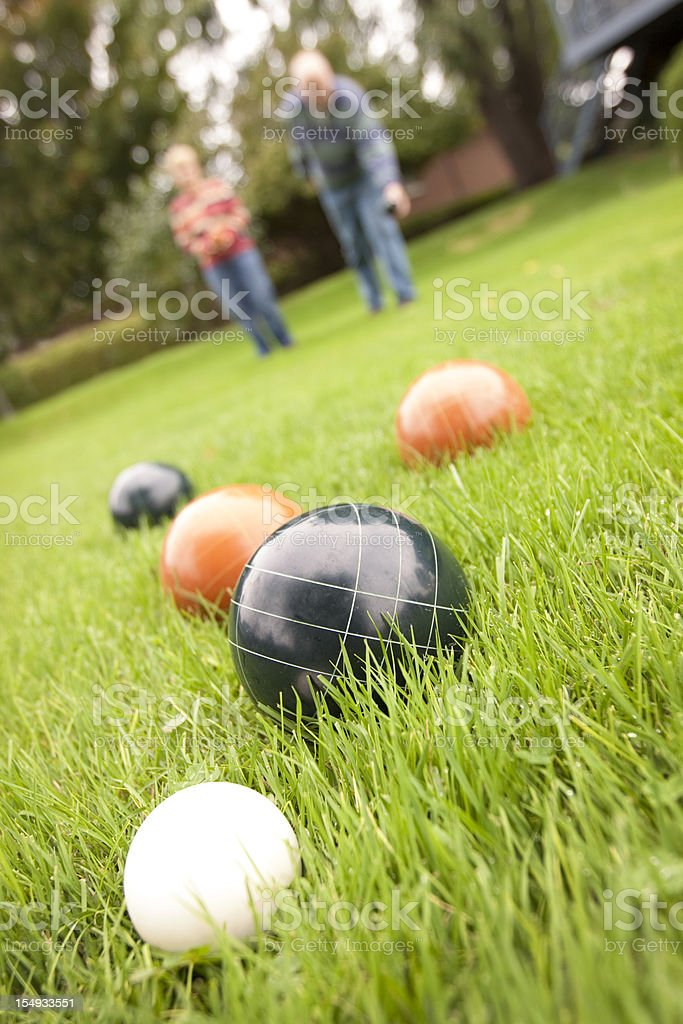 Couple playing bocce ball in grass stock photo