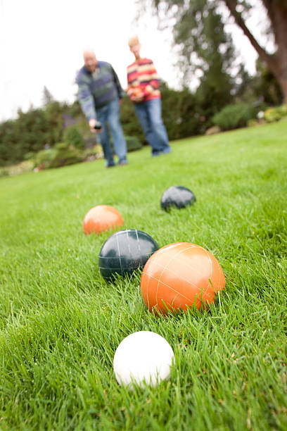 Couple playing bocce ball - vertical stock photo