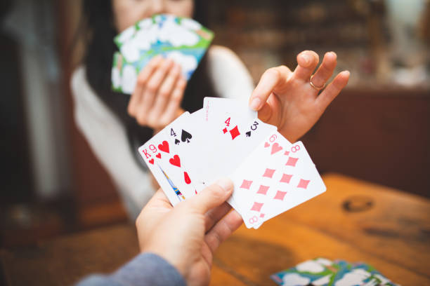 Couple playing cards at home stock photo