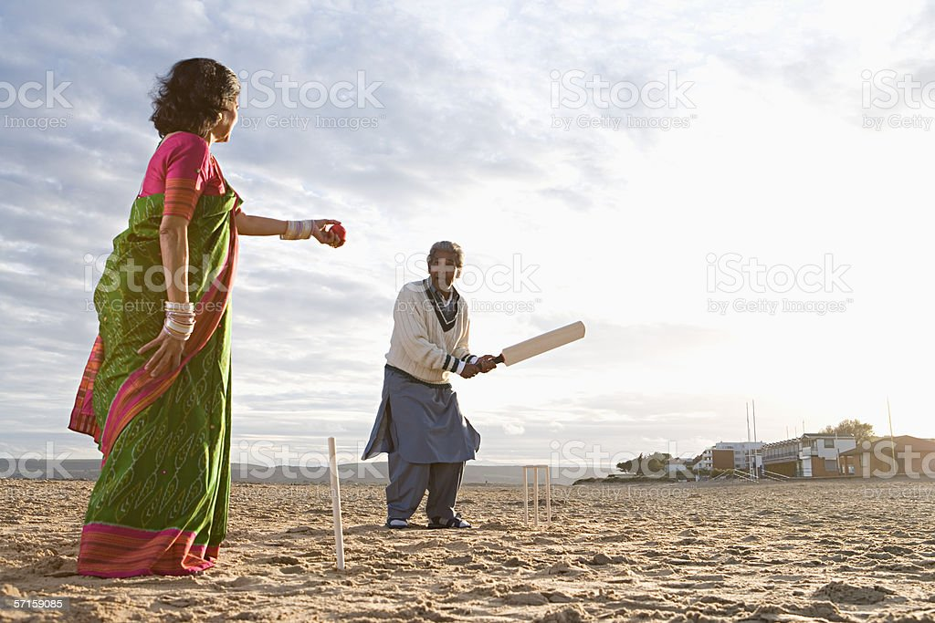 Couple playing cricket on the beach stock photo