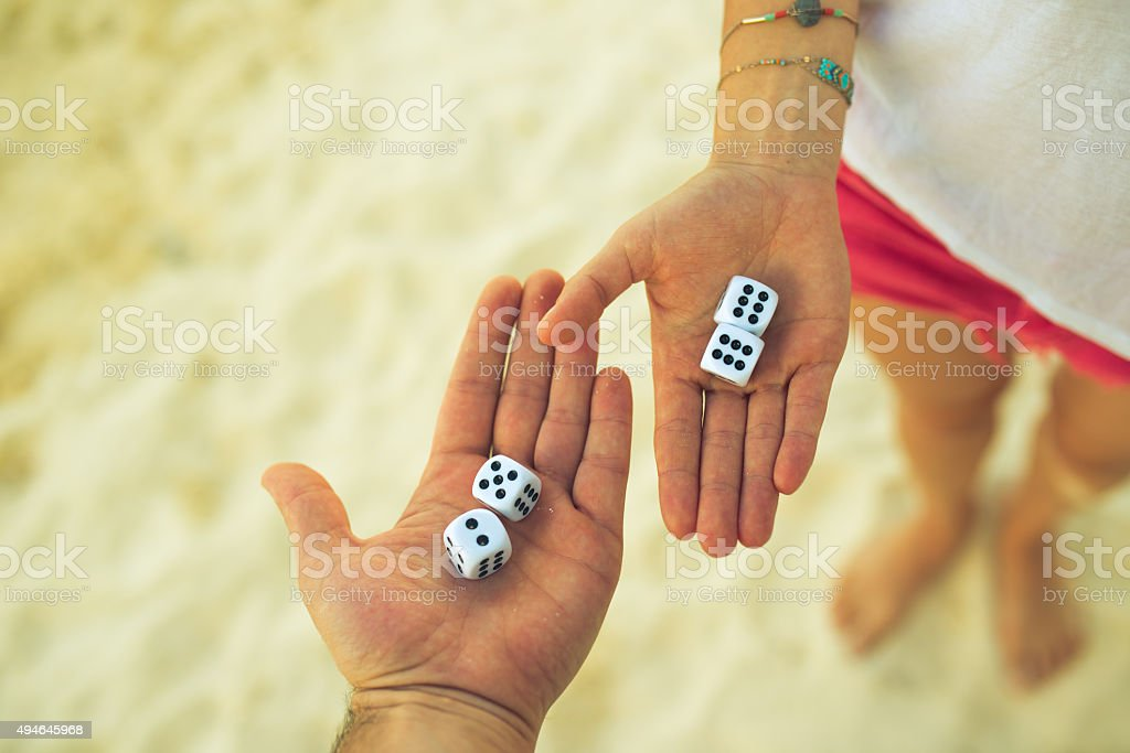 couple playing dice on the beach stock photo