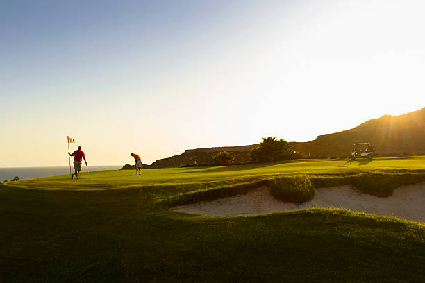 A couple playing golf on a putting green Landscape image of two golfers playing while in the green of a golf course. green golf course stock pictures, royalty-free photos & images