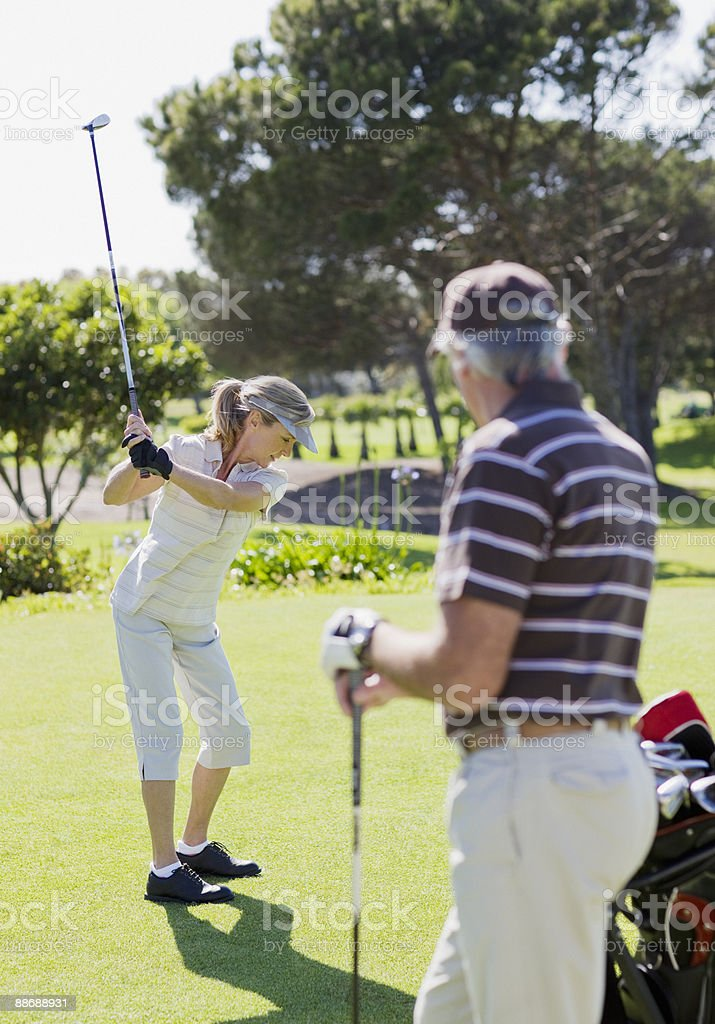 Couple playing golf royalty-free stock photo