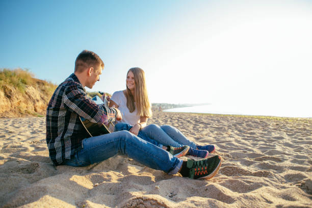 couple playing guitar on beach young caucasian couple playing guitar on beach during sunset or sunrise serenading stock pictures, royalty-free photos & images