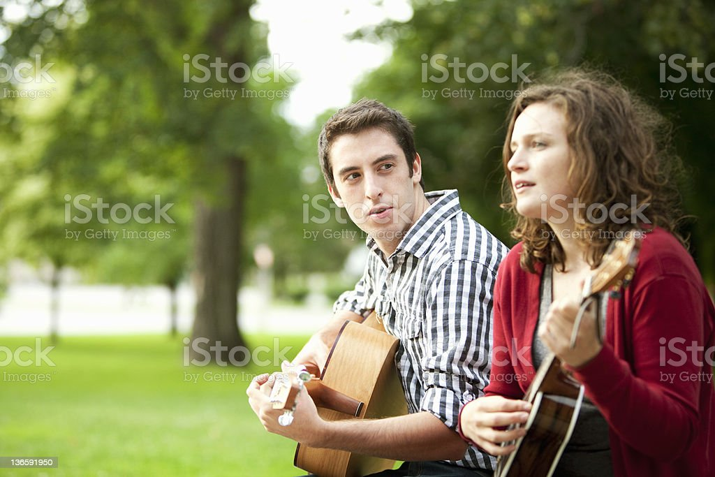 Couple playing guitars in park stock photo