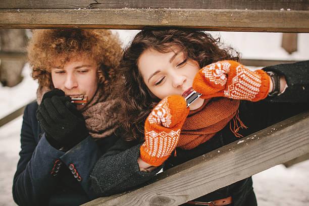 Paar spielt Mundharmonika gemeinsam im winter im Freien – Foto