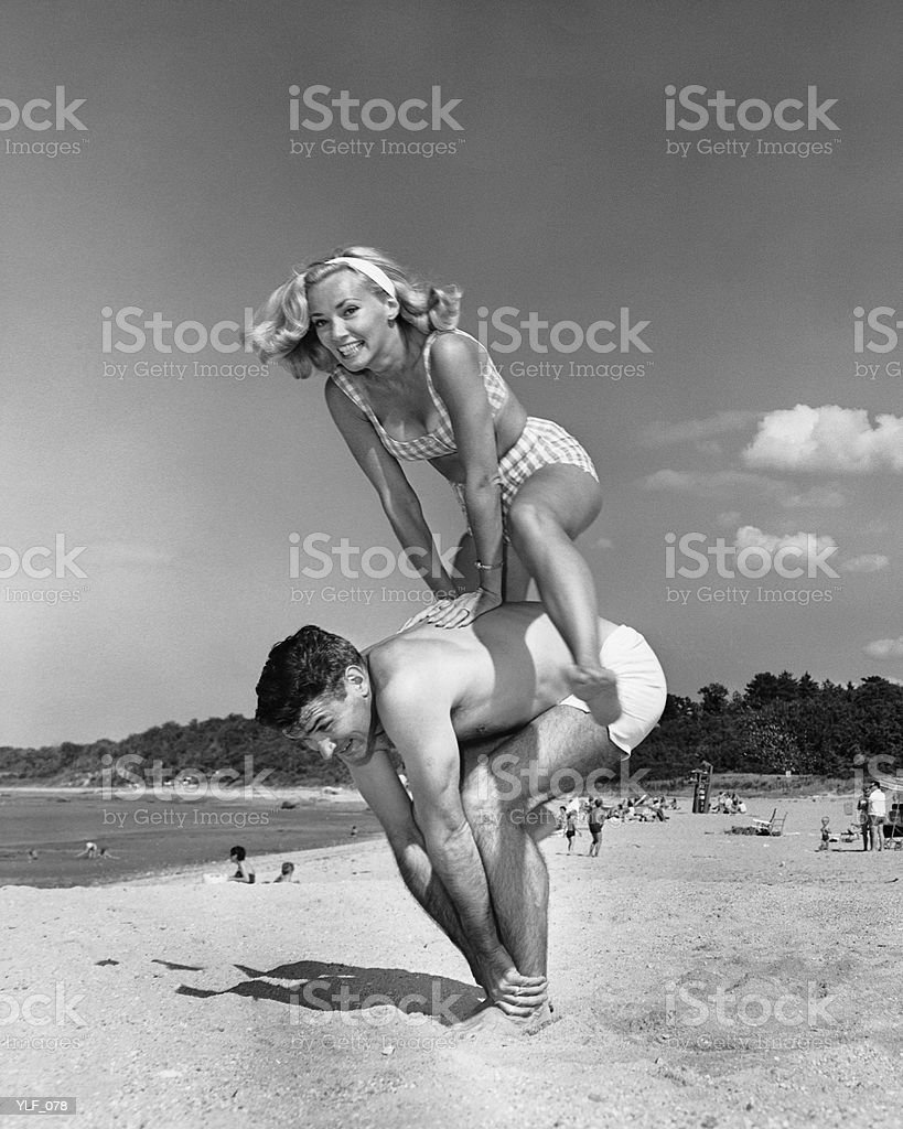Couple playing leapfrog on beach royalty-free stock photo