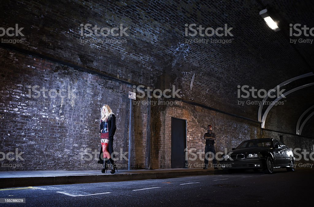 Couple playing master and servant in a dark highway tunnel. stock photo