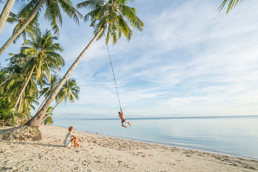Couple playing on beach, swing rope on palm tree in tropical Island Asia