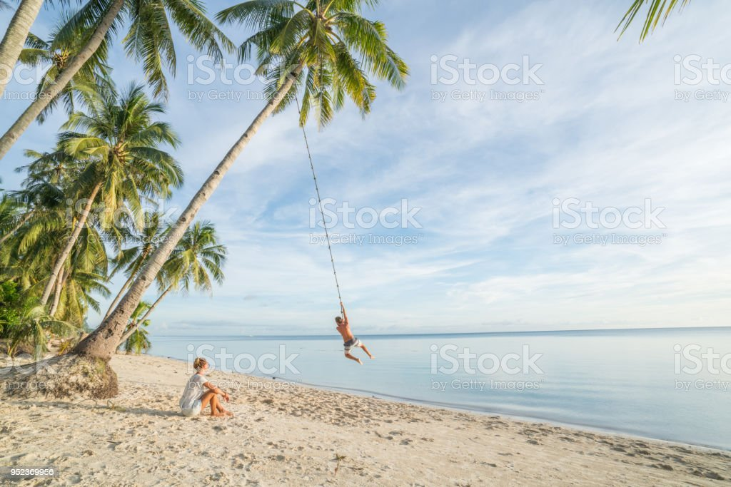 Paar am Strand, Schaukel Seil auf Palme im tropischen Insel Asien spielen – Foto