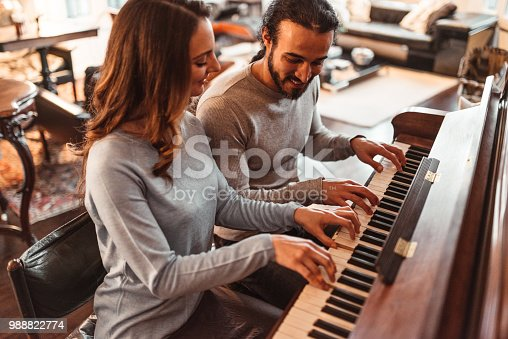 couple playing piano in a lux apartment