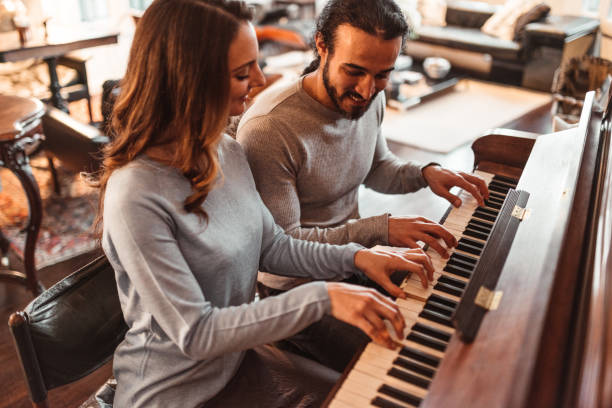 couple playing piano in a lux apartment couple playing piano in a lux apartment pianist stock pictures, royalty-free photos & images