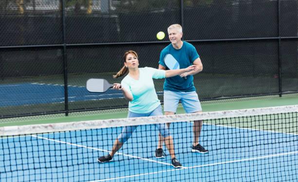 Couple playing pickleball, Hispanic woman hitting ball stock photo