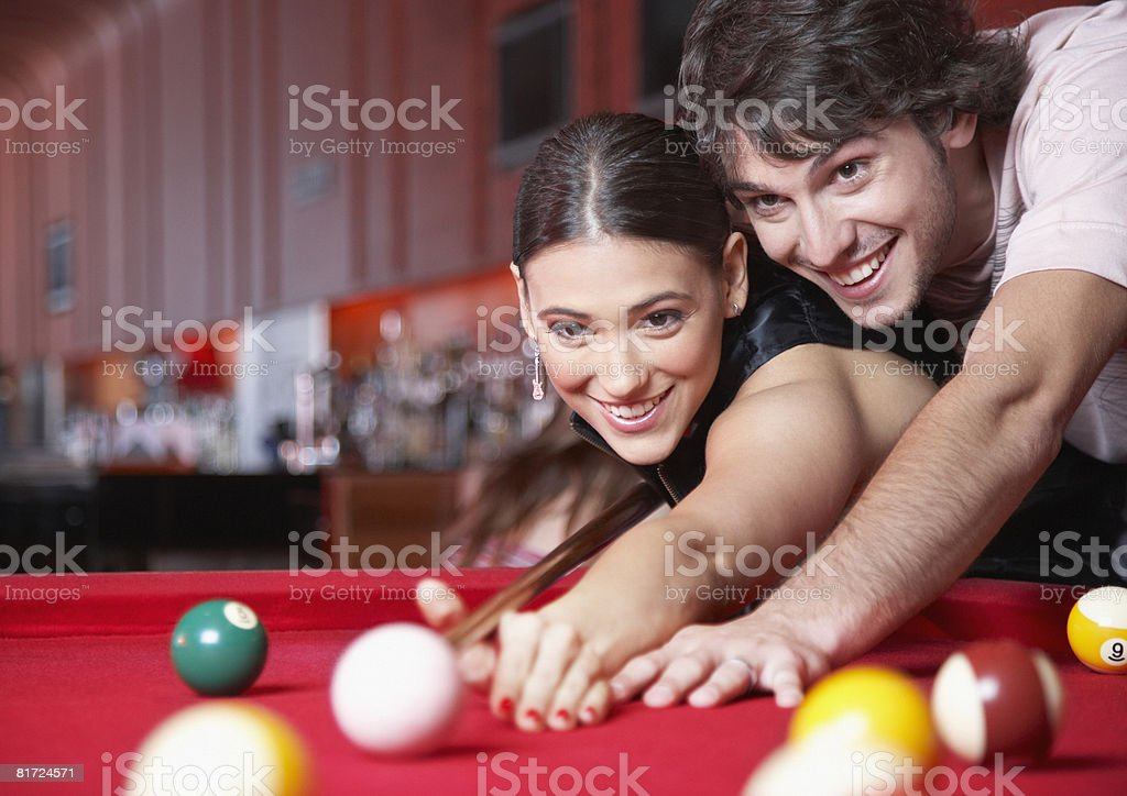 Couple playing pool and smiling royalty-free stock photo