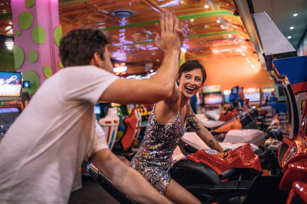 Couple playing racing games sitting on arcade racing bikes stock photo
