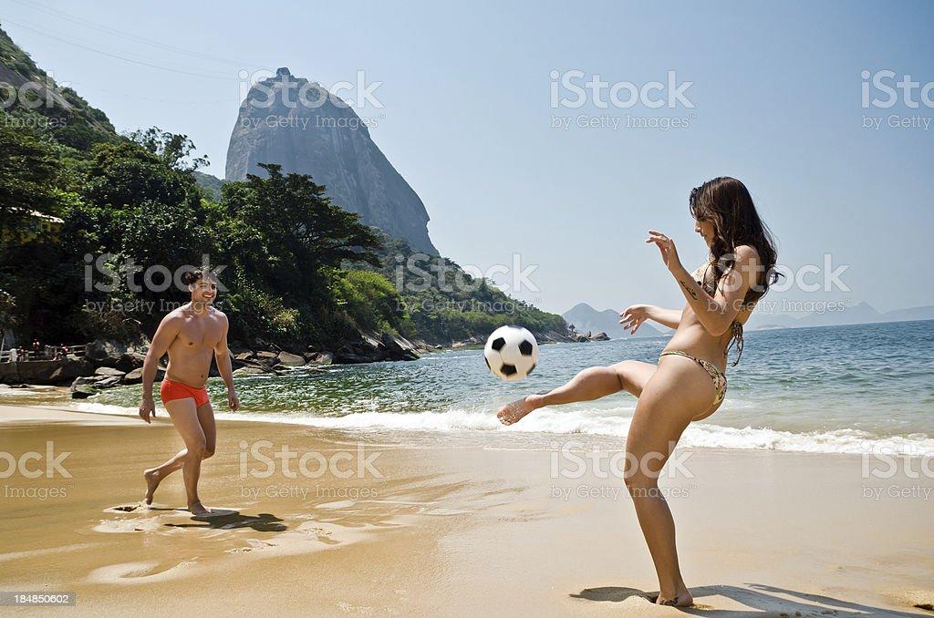 Casal jogando futebol na praia - foto de acervo