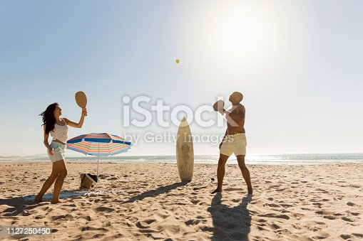 Full length of happy young couple playing table tennis at beach. Female is enjoying with boyfriend on sunny day against sky. Both are on summer vacation.