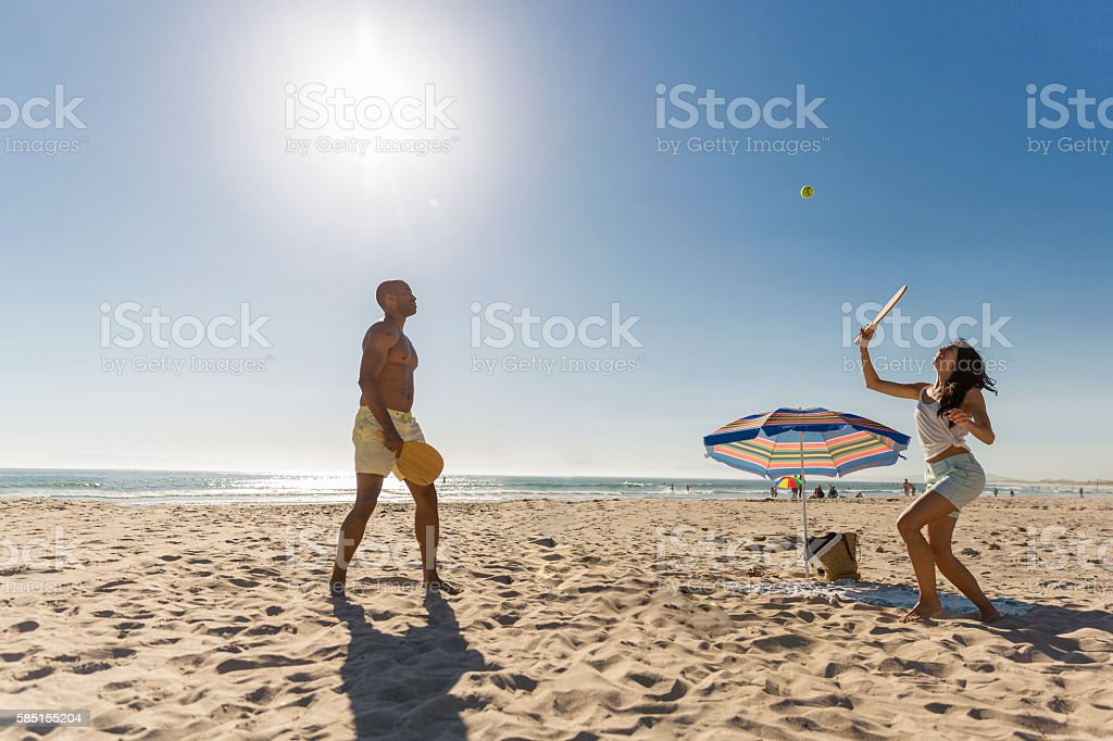 Couple playing tennis at beach against clear sky stock photo