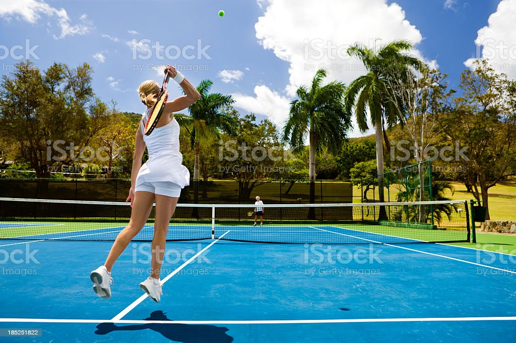 couple playing tennis in a tropical setting royalty-free stock photo