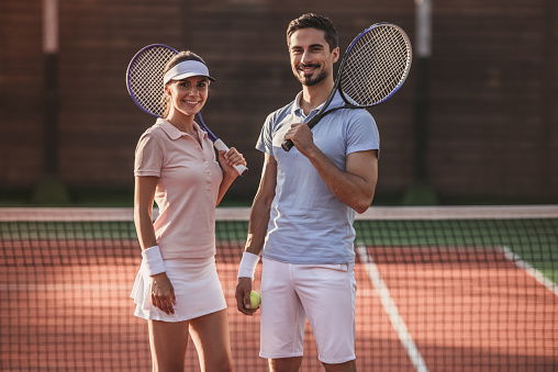Handsome man and beautiful woman are looking at camera and smiling while playing tennis on tennis court outdoors