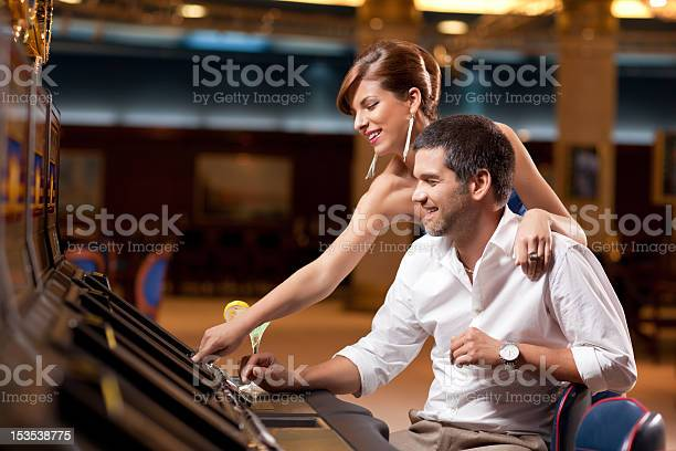 Couple playing the slot machine in a casino picture id153538775?b=1&k=6&m=153538775&s=612x612&h= v bbea03hnvk6 dlnfj ap18prnwha6khkv6oxrei0=