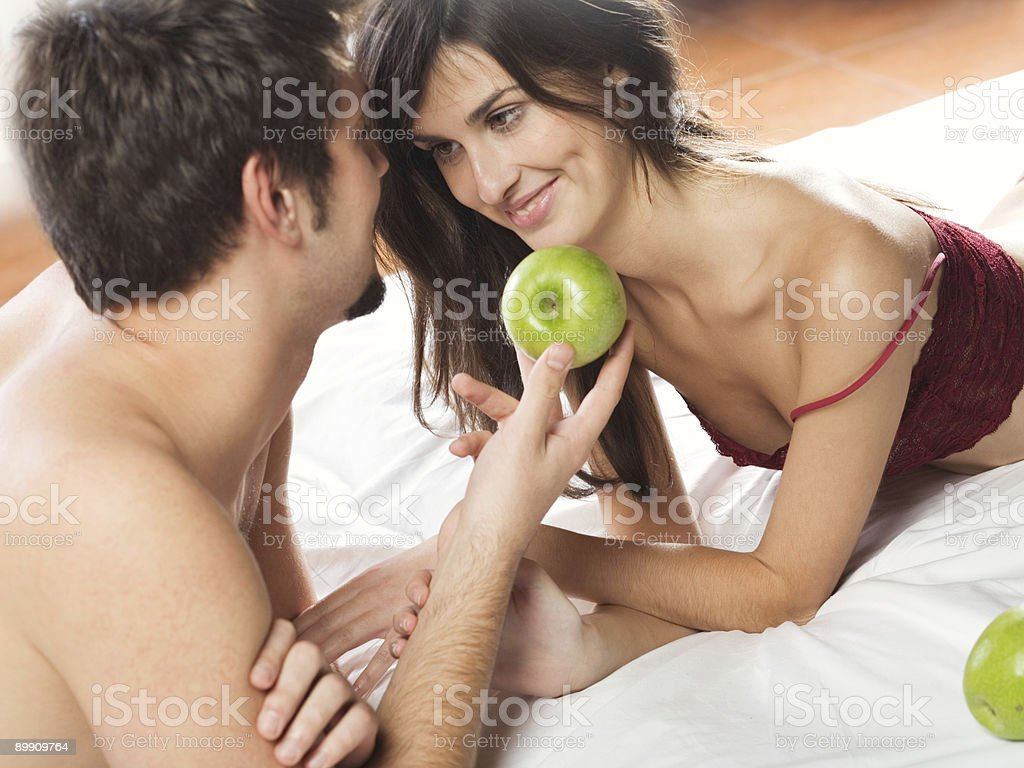 Couple playing with apple on the bed in bedroom stock photo