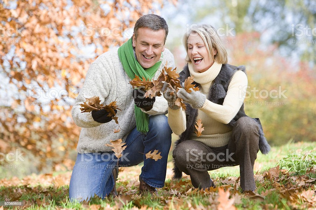 A couple playing with leaves in autumn royalty-free stock photo