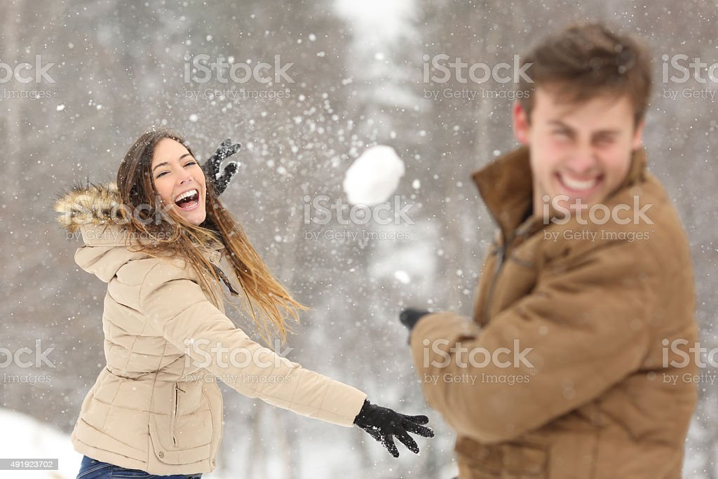 Couple playing with snow and girlfriend throwing a ball stock photo