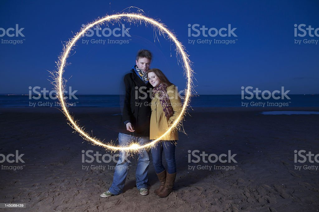Couple playing with sparkler on beach stock photo