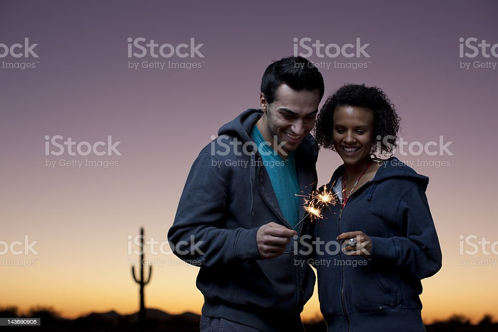 Couple playing with sparklers in desert stock photo