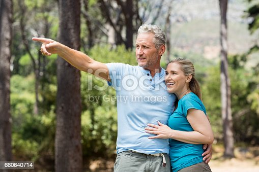 Couple pointing and holding each other on the wood