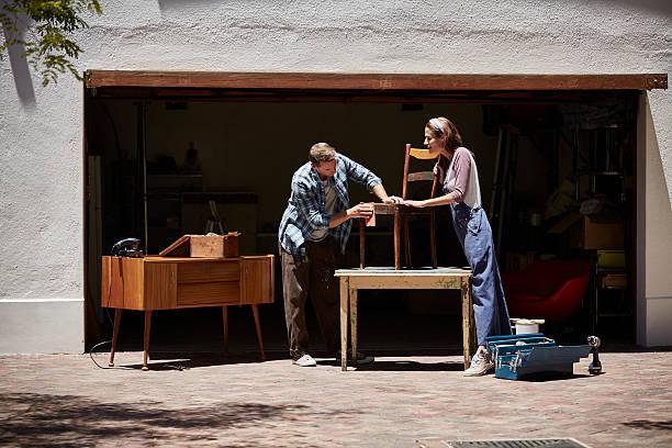 Couple polishing chair outside house stock photo