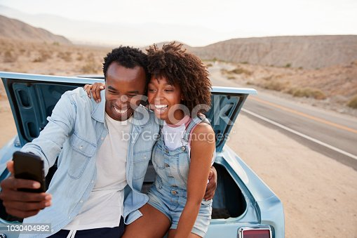 1030408008 istock photo Couple Posing For Selfie Sitting In Trunk Of Classic Car On Road Trip 1030404992