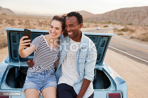 1030408008 istock photo Couple Posing For Selfie Sitting In Trunk Of Classic Car On Road Trip 1030404998